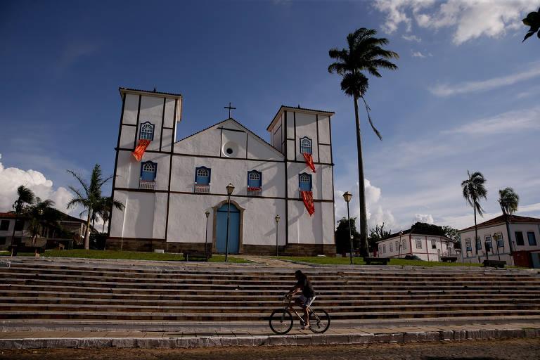 Imagem mostra uma igreja, de arquitetura no estilo colonial, pintada com tinta branca,  sob sol da tarde, na cidade histórica de Pirenópolis. O templo está cercado por palmeiras e outras construções do período colonial. Em primeiro plano, após as escadarias da igreja, uma pessoa passa de bicileta
