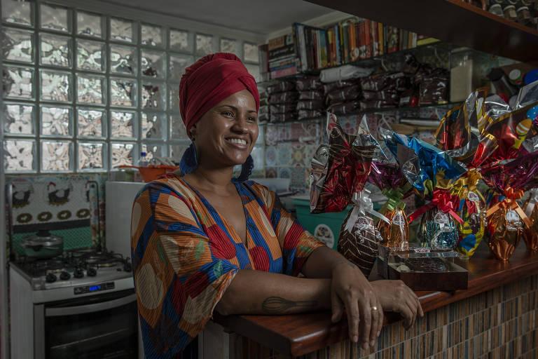 Mulher negra posa sorridente em uma cozinha ao lado de ovos de Páscoa com embalagens coloridas