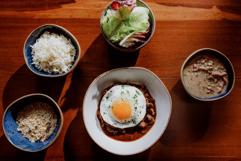 Pratos do delivery do restaurante Tujuína, na Vila Madalena, entre eles  picadinho de carne com ovo frito, arroz basmati, feijão-manteiguinha com linguiça e farofa crocante e pão de abóbora