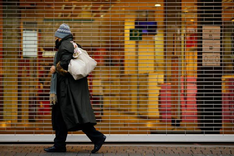Mulher com máscara caminha em frente a loja fechada em Colônia, na Alemanha