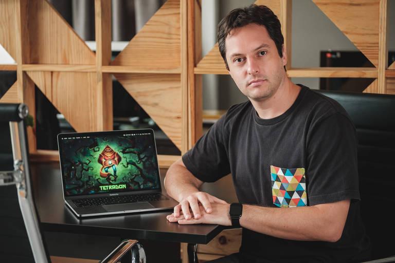 Homem branco está sentado ao lado de um laptop