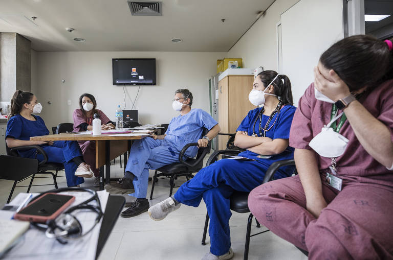 médicos sentados em roda conversando; eles parecem cansados e abatidos. uma das médicas, em primeiro plano, segura a cabeça com as mãos, como se estivesse chorando