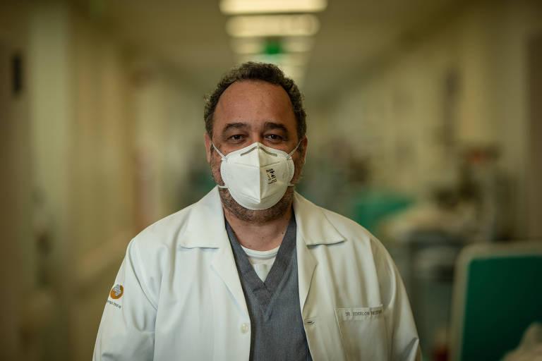 Ederlon Rezende usa máscara branca e avental. Ele está no corredor de um hospital; ao fundo, à direita da foto, há macas