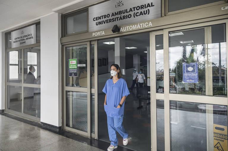 Médica de uniforme azul e máscara branca, com as mãos nos bolsos, em frente à porta onde, no alto, se lê 'Centro Ambulatorial Universitário'