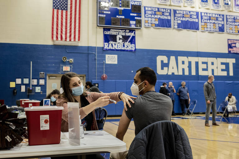 Profissional da saúde aplica a vacina contra a Covid-19 em um evento de imunização em massa para professores em Nova Jersey