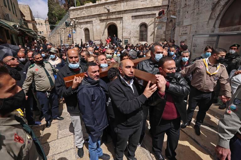 Fiéis carregam uma cruz de madeira em Jerusalém