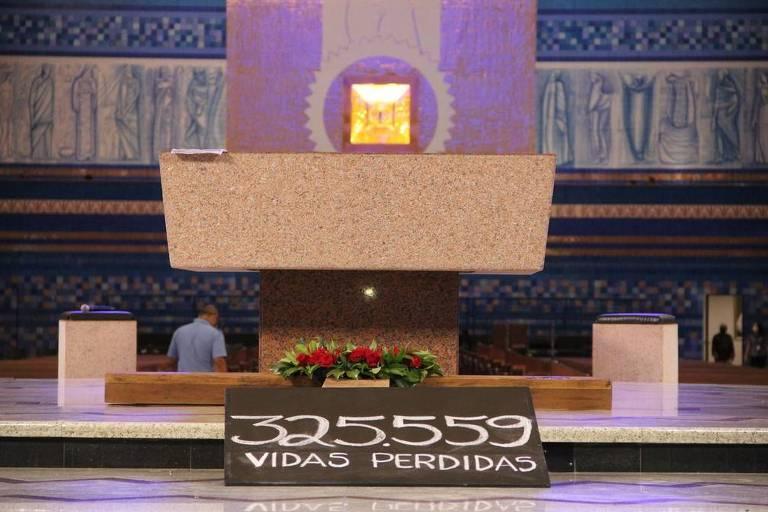 """Imagem mostra placa com os dizeres """"325.559 vidas perdidas"""" durante encenação da Paixão de Cristo"""