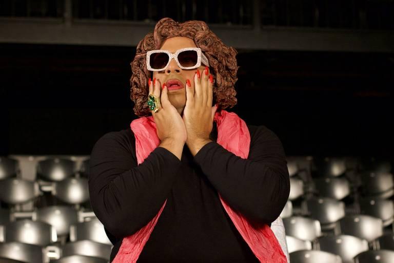 Luis Lobianco, usando peruca, óculos escuros e um lenço rosa, olha para frente com cara de espanto e as mãos no rosto. Cadeiras de teatro aparecem ao fundo