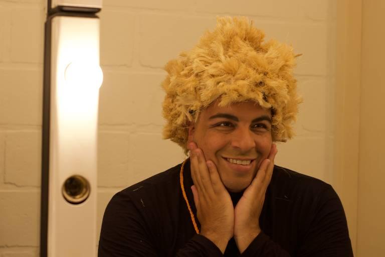 Ator aparece sorrindo, com as mãos no rosto e com uma peruca de cabelo curto loira