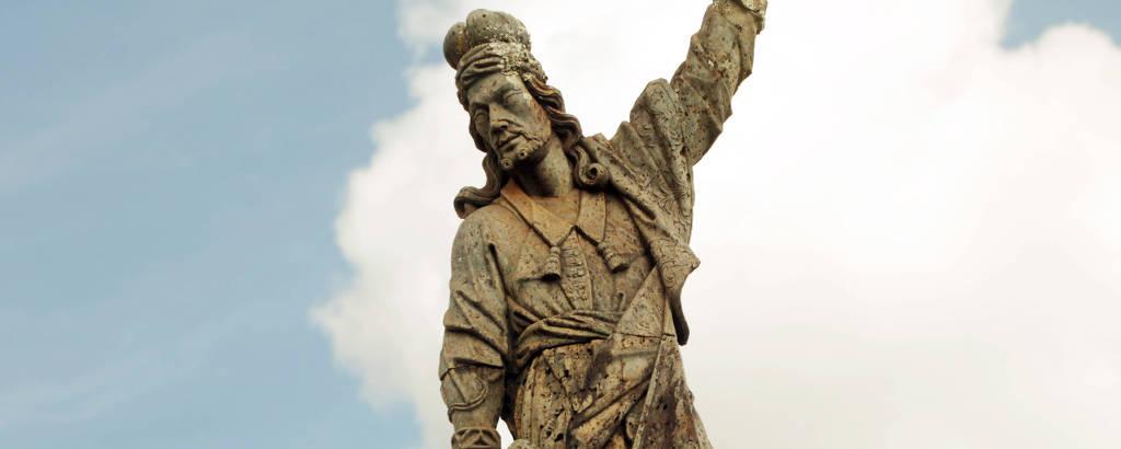 Estátua do profeta Habacu, que tem a mão esquerda levantada; ao fundo, vê-se o céu azul com poucas nuvens