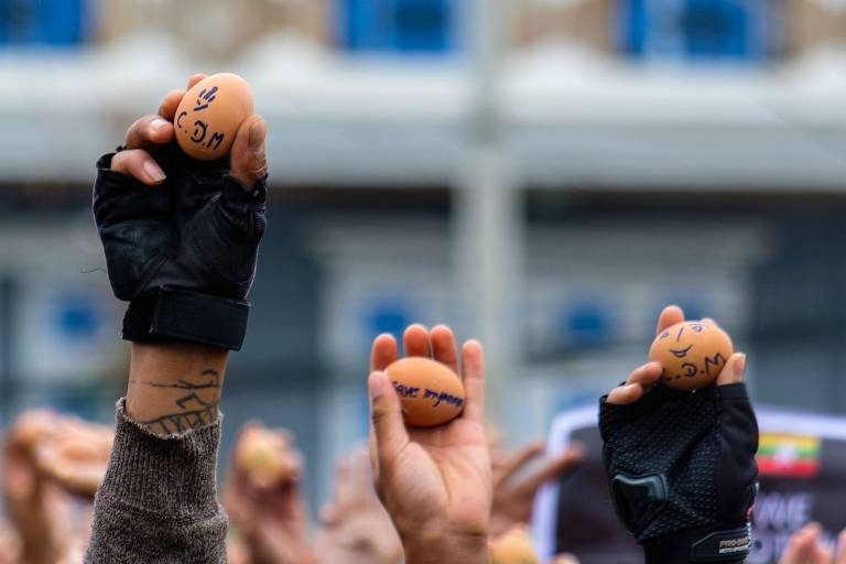 Manifestantes em Mianmar mostram ovos com mensagens contra o golpe de Estado, durante protestos no domingo (4)