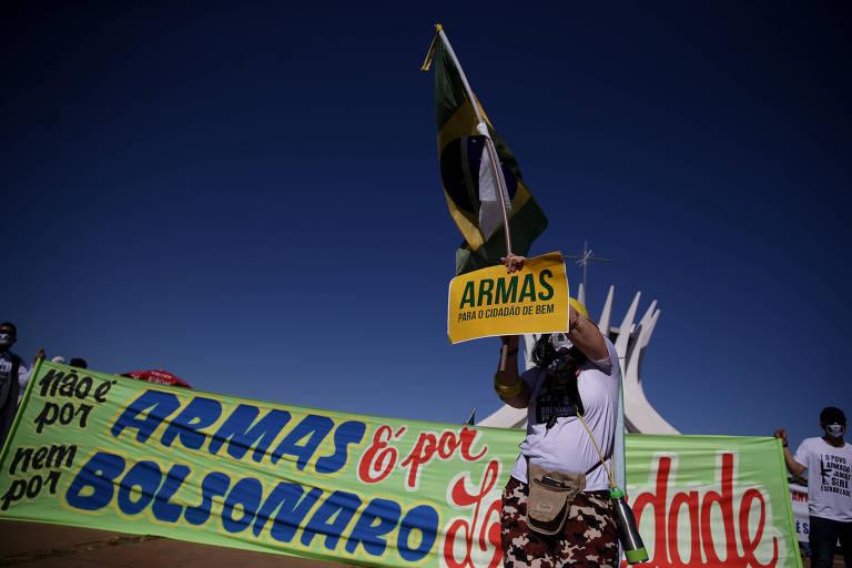 """Pessoa segura um cartaz com a frase """"Armas para o cidadão de bem"""" e uma bandeira do Brasil em frente a uma faixa que diz """"Não é por armas nem por Bolsonaro. É por liberdade"""". Ao fundo, a Catedral Metropolitana de Brasília"""