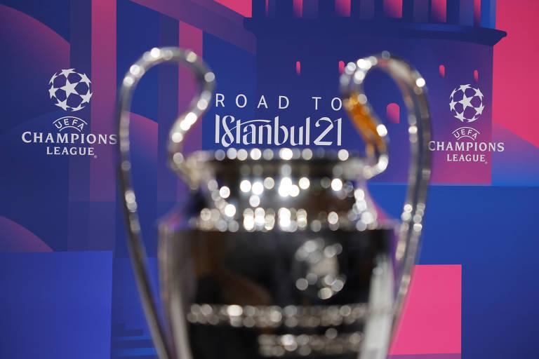 """Troféu em primeiro plano, à frente de parede de fundo roxo e rosa e a frase """"rota para Istambul 21"""""""