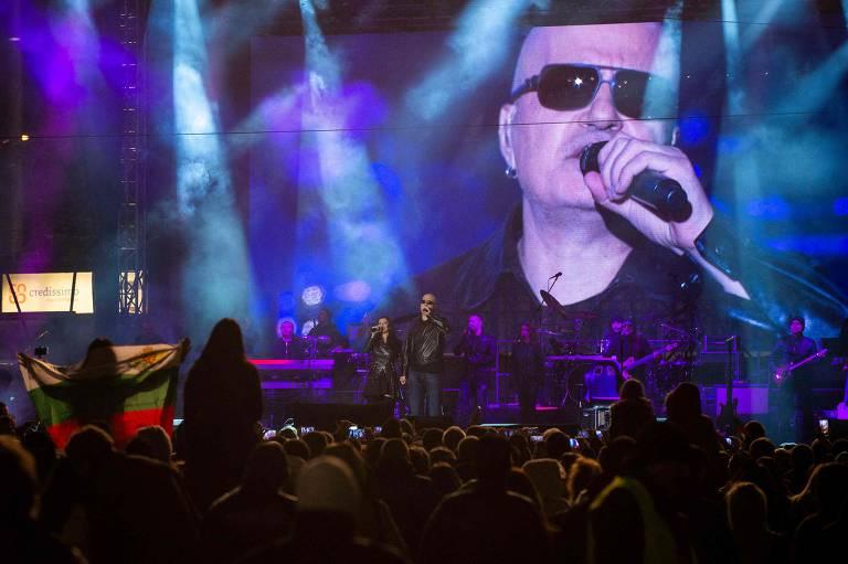 Telão mostra homem de óculos escuros cantando ao microfone