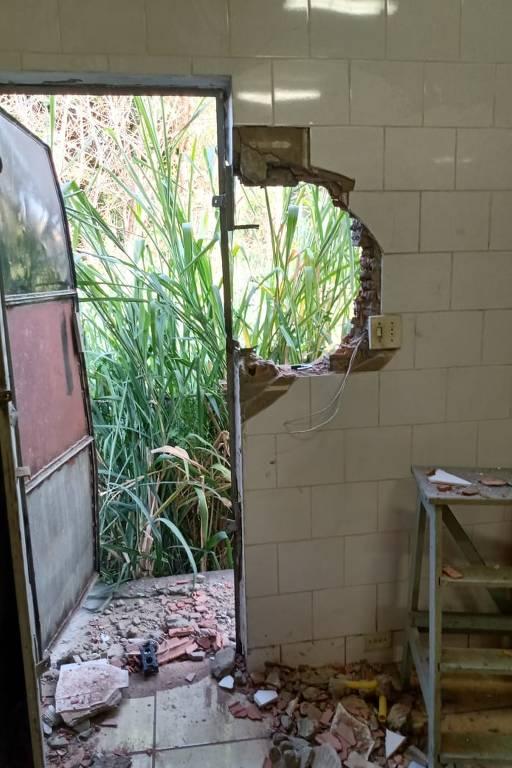 Imagem mostra porta arrombada e parte da parede de imóvel destruída
