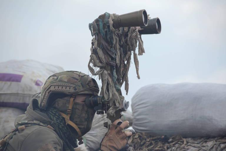 Soldado ucraniano usa binóculos adaptados para observar linhas rebeldes perto de Donetsk