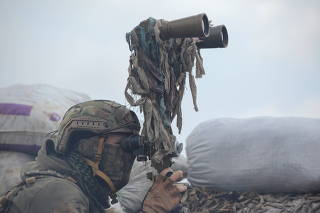 A service member of the Ukrainian armed forces uses binoculars while observing the area at fighting positions near the rebel-controlled city of Donetsk