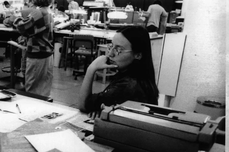 retrato em preto e branco de mulher branca, de cabelos pretos lisos e óculos, sentada em uma escrivaninha, rodeada de papeis