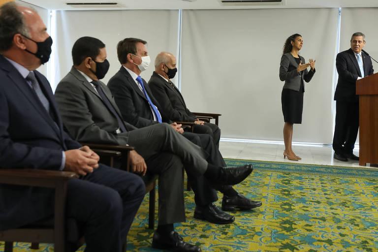 O presidente e ministros sentados acompanhando a fala de Braga Netto