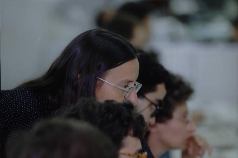 mulher de cabelos pretos lisos se inclina por cima do ombro de três pessoas