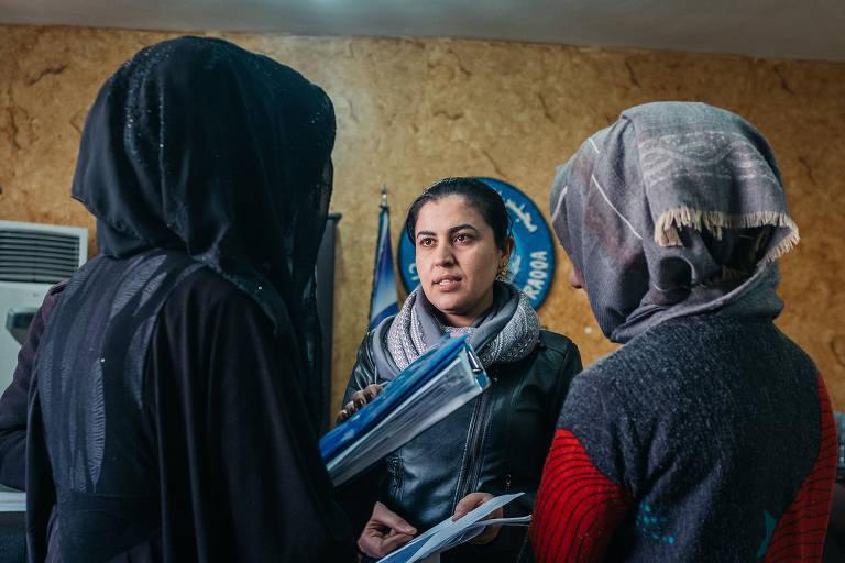 Três mulheres se encaram segurando pastas nos braços