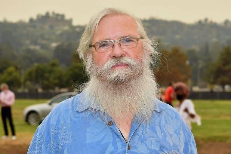 Homem branco barbudo sorri para foto