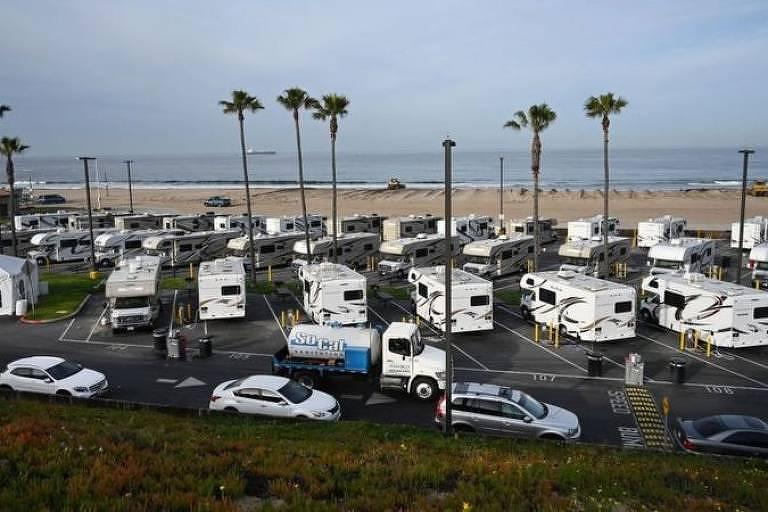 Vários trailers lado a lado estacionados próximos a uma praia