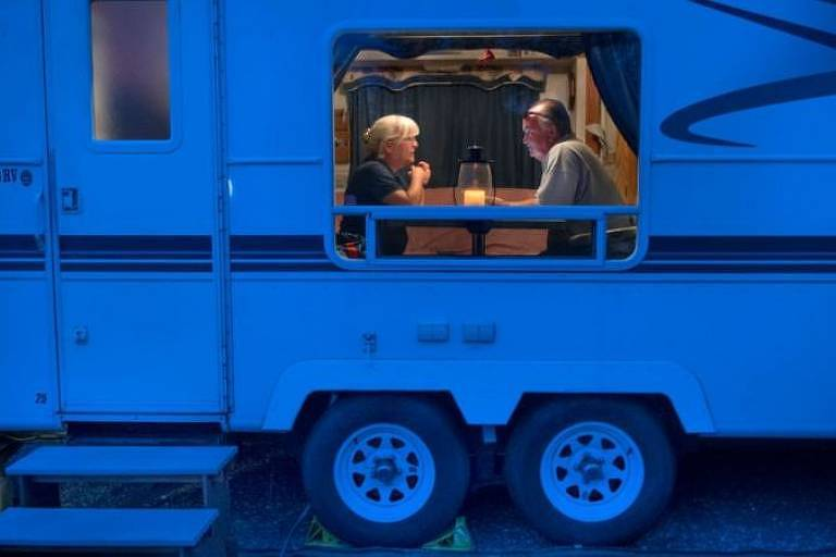 Trailer iluminado por luz azulada revela (através da janela) um homem e uma mulher conversando num trailer