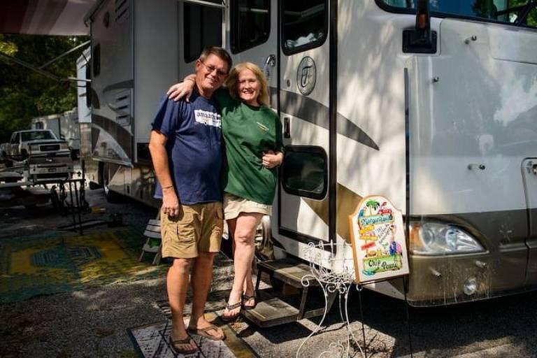 Um homem e uma mulher brancos abraçados em frente a um trailer