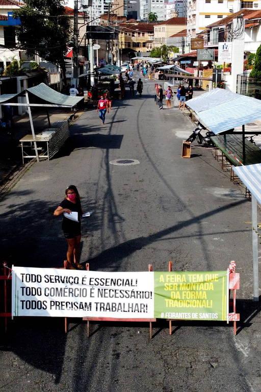 """Em Santos, no litoral paulista, feirantes protestaram contra medidas mais rigorosas da prefeitura em relação à volta das feiras livres na cidade; em um cartaz há os dizeres: """"Todo serviço é essencial! Todo comércio é necessário! Todos precisam trabalhar!"""""""