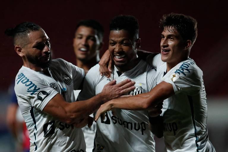 Marinho (no centro) é abraçado após marcar o segundo gol do Santos contra o San Lorenzo