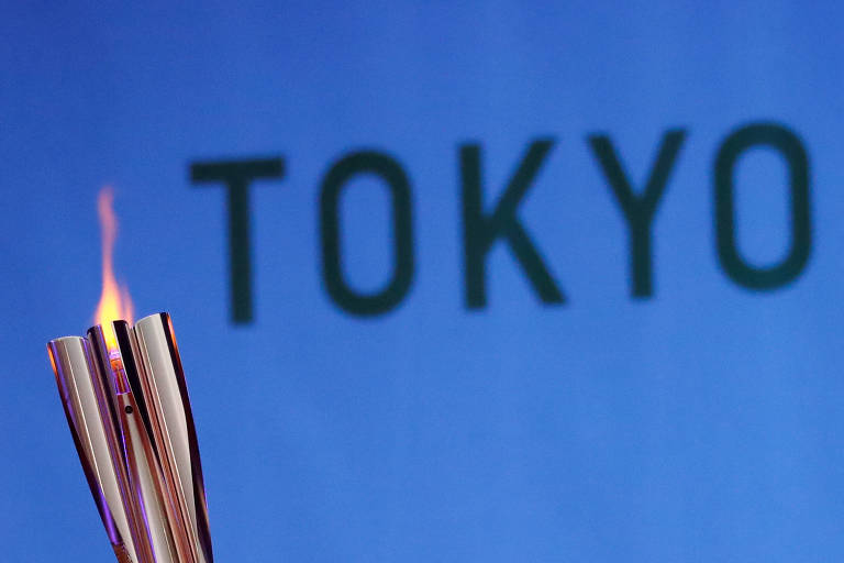 Tocha acesa em frente a banner com a palavra Tokyo