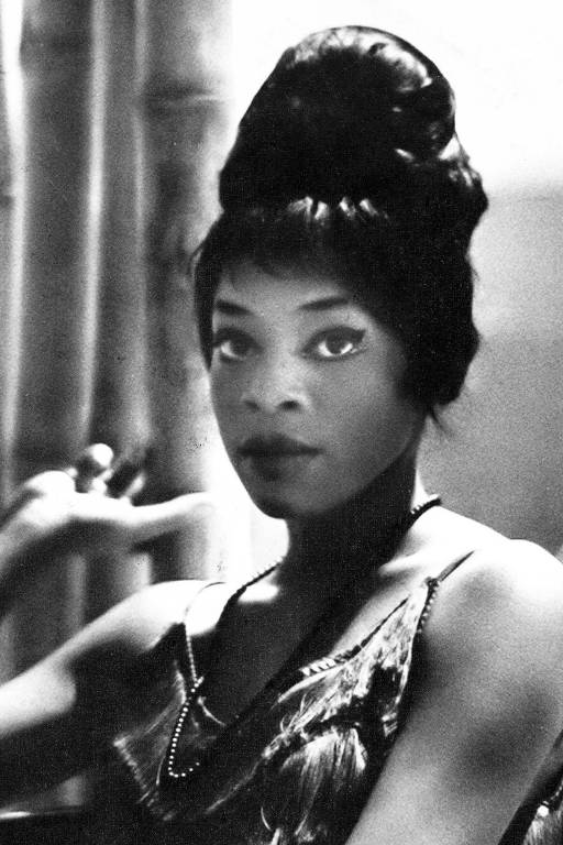 Mulher jovem negra olha para câmera