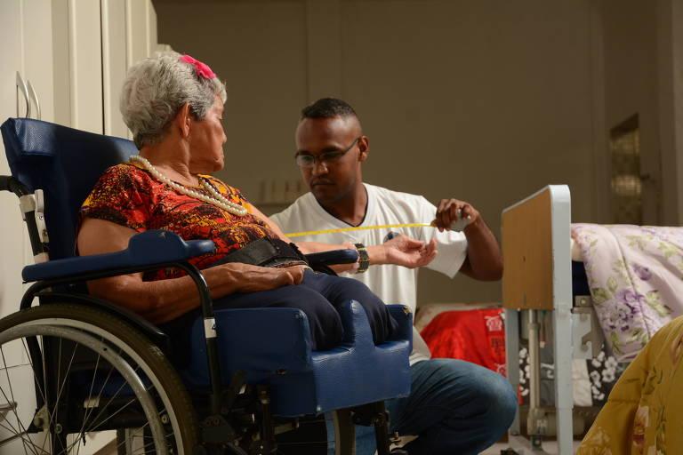 homem jovem e negro, vestido de branco, ajoelhado em frente à mulher branca e idosa em cadeira de rodas