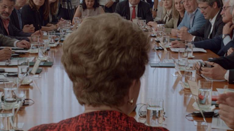 Vemos uma mesa com pessoas de ambos os lados e, em primeiro plano, na cabeceira, de costas para a câmera, Dilma