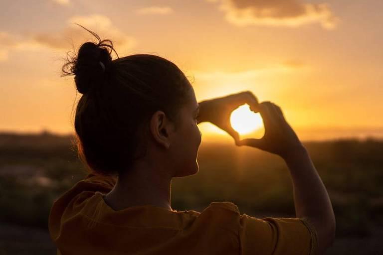 Silhueta contra-luz de mulher, com coque, fazendo sinal de coração com as mãos em direção ao pôr-do-sol