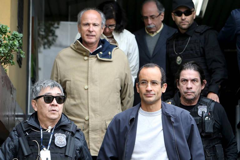 Um homem jovem de óculos e outro mais velho de casaco acompanhados por agentes da Polícia Federal na saída do Instituto Médico Legal de Curitiba