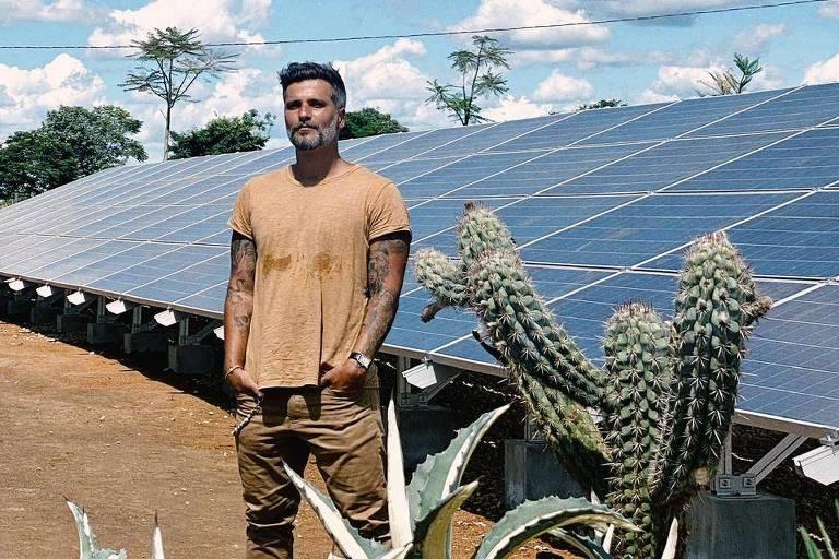 Bruno Gagliasso em frente a painéis de energia solar