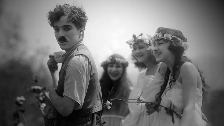 Homem branco com bigode em frente a três mulheres jovens brancas que riem