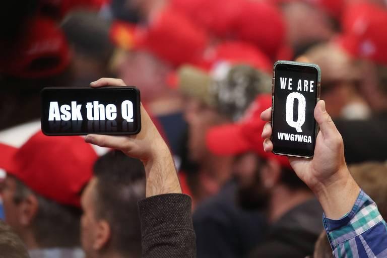 Apoiadores de Donald Trump mostram tela de celular com referências à teoria da conspiração QAnon durante evento de campanha em Las Vegas