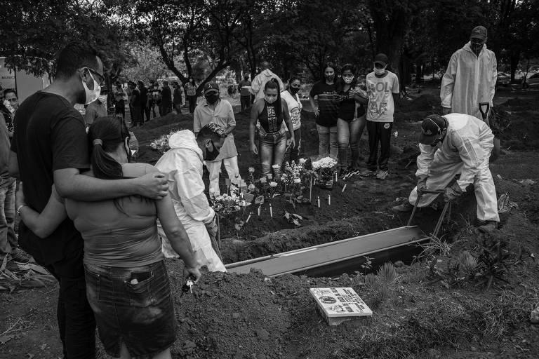 Familiares olham caixão sendo colocado, por sepultadores, em uma cova
