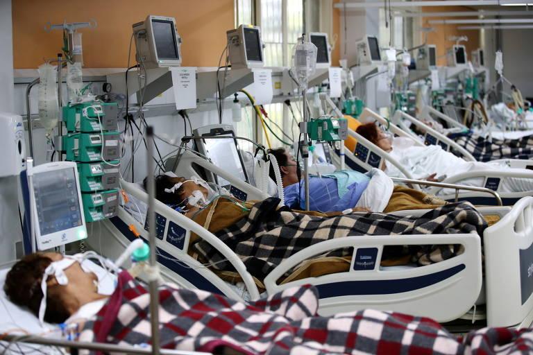 Fila de leitos de UTI com pacientes em sala superlotada.