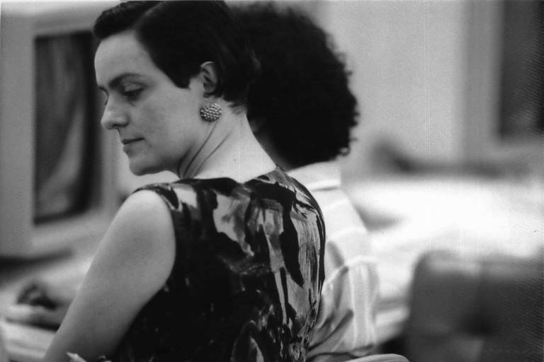retrato em preto e branco de mulher sentada, de costas, tentando olhas para trás