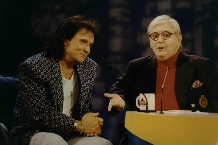 Dois homens lado a lado conversando sentados numa poltrona
