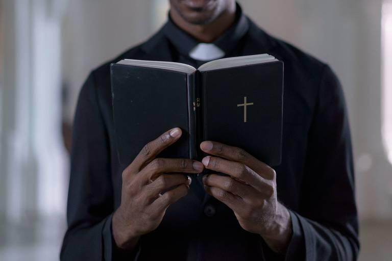 Jovem negro, em vestes de pastor, segura e lê uma bíblia aberta, de capa preta.