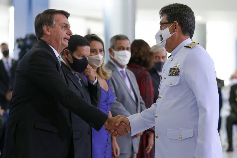 Sem máscara, o presidente Jair Bolsonaro cumprimenta militar durante cerimônia no Palácio do Planalto