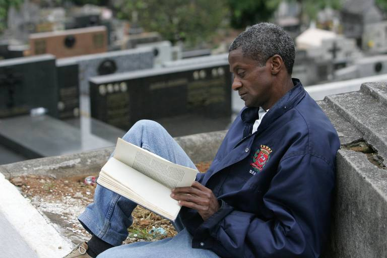 homem sentado lendo um livro no cemitério