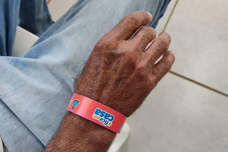 Imagem mostra braço de homem com pulseira vermelha, que significa que ele foi diagnosticado com o novo coronavírus