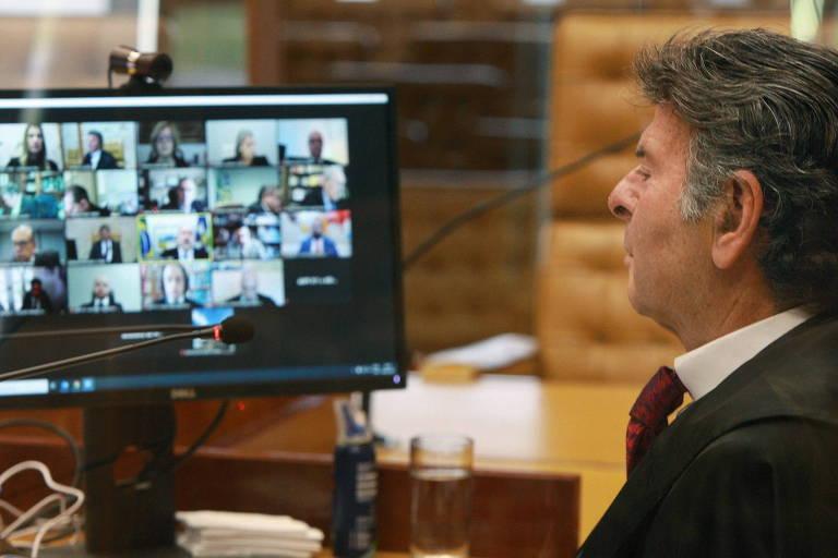 À esquerda um monitor onde se vê a tela dividida com a imagem dos demais ministros, à direita o ministro Luiz Fux sentado no plenário do STF.