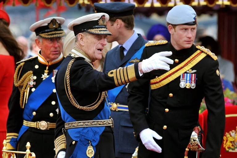 Entre o príncipe Charles, à esq., e o príncipe Harry, à dir., Philip gesticula durante evento em Londres